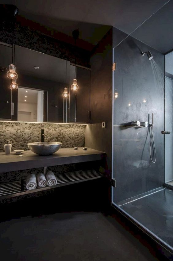 a matta black contemporary bathroom with a shower, pendant lamps, a concrete vanity and a vessel sink