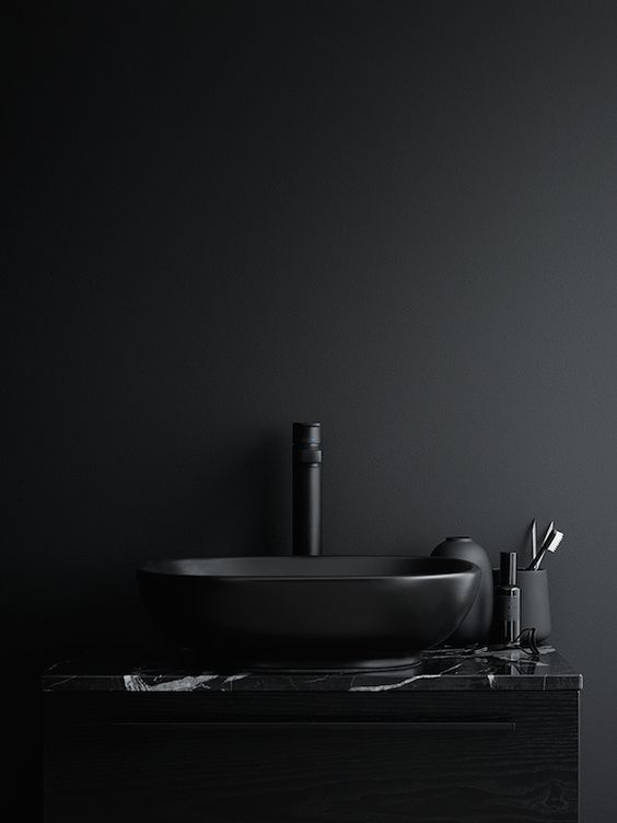 a matte black sink and faucet plus a black marble countertop for a refined modern look