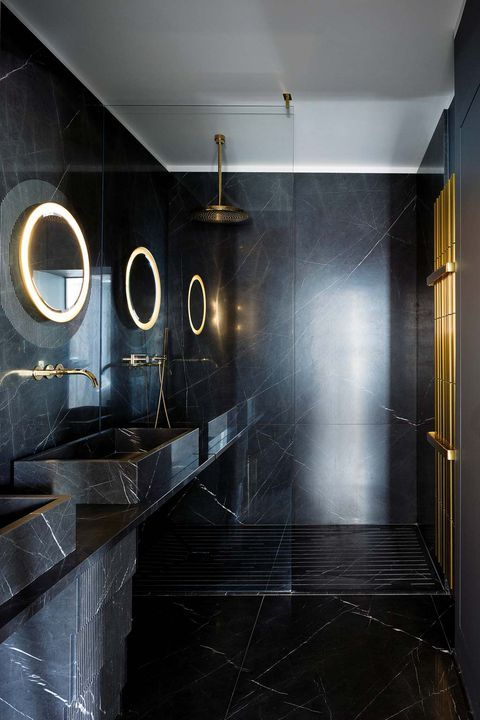 a stylish modern bathroom in black done with marble and stone, with lit up mirrors and brass touches
