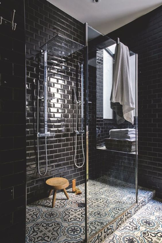 an elegant black bathroom with glossy subway tiles with white grout and a mosaic tile floor
