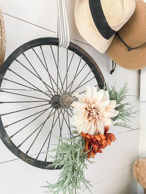 DIY old bike wheel wreath with fake blooms (via www.twelveonmain.com)