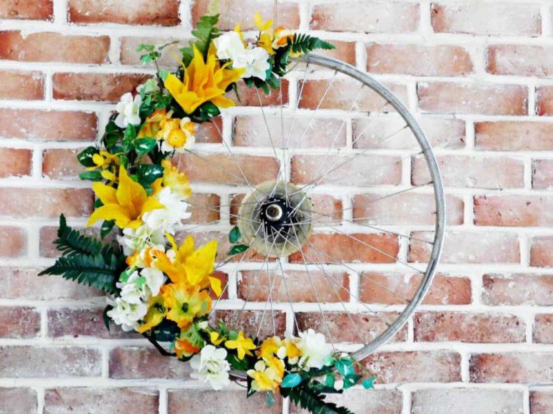 DIY colorful bike wheel wreath with fake blooms (via www.craftylittlegnome.com)