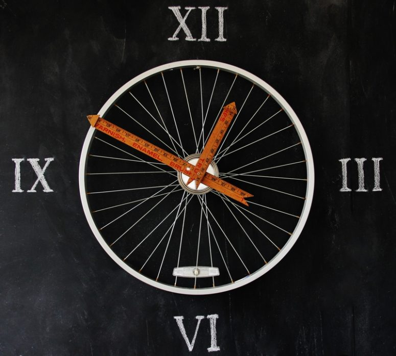 DIY bike wheel clock with Roman numbers on the wall (via thistlewoodfarms.com)