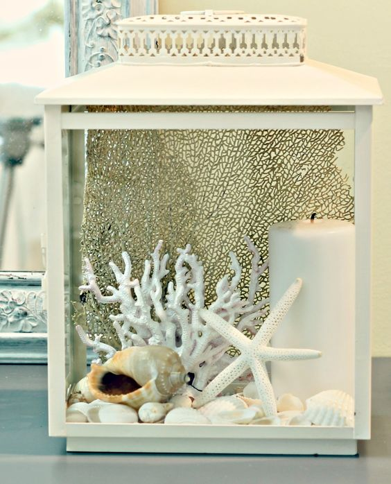 a beachy lantern with corals, starfish, seashells, pebbles and a pillar candle looks very cute