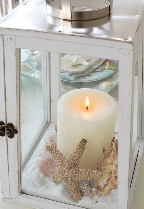 a beach lantern with sand, seashells and starfish plus a pillar candle in the center