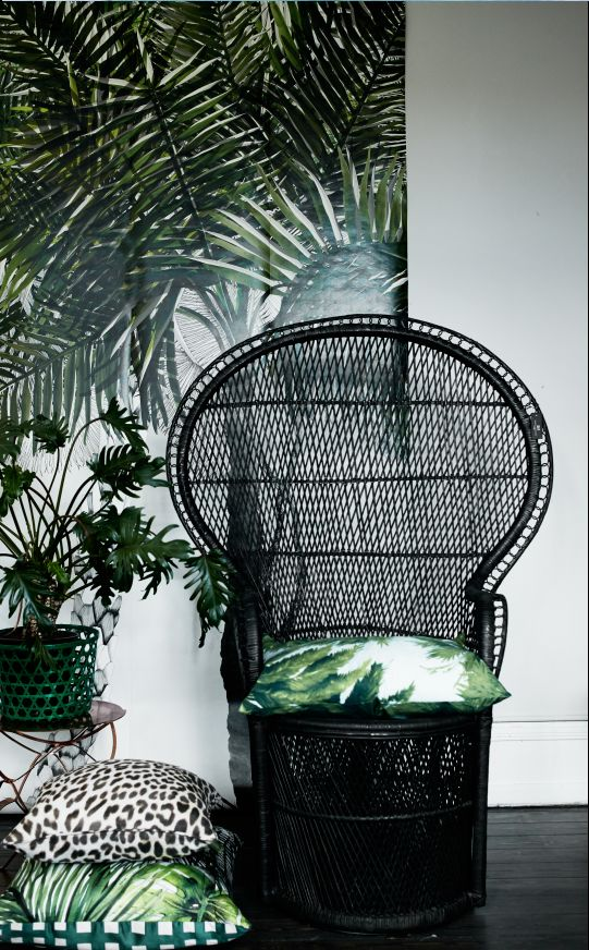 a black peacock rattan chair with a bright tropical print pillow is a chic idea for a tropical feel