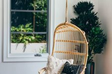 05 a hanging rattan chair with pillows and some faux fur for adding a boho touch to the space