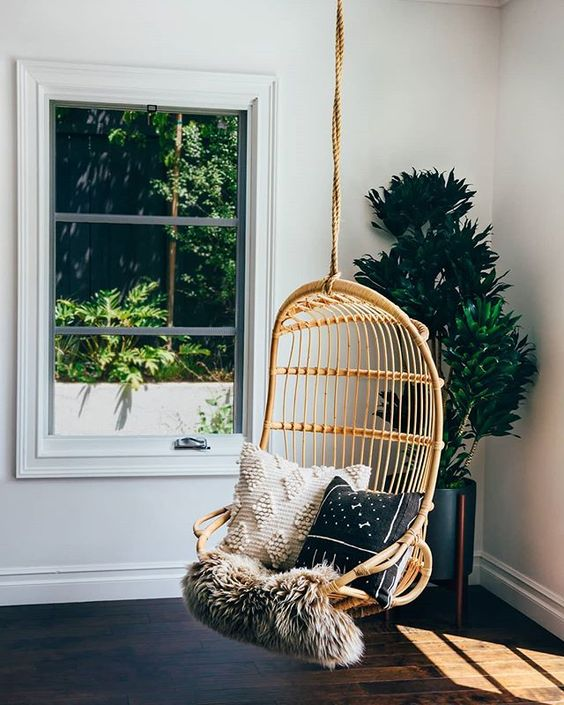 a hanging rattan chair with pillows and some faux fur for adding a boho touch to the space