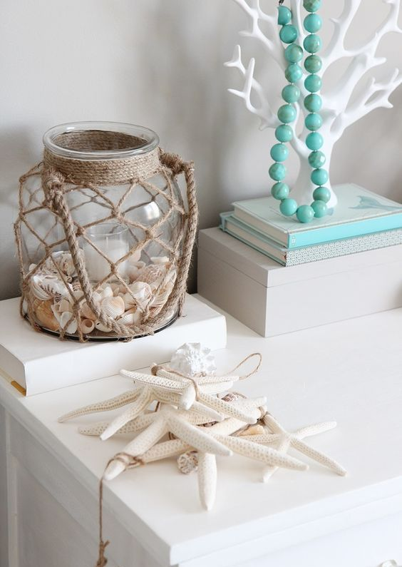 a twine wrapped lantern with seashells and a candle in the center feels very coastal and inspiring