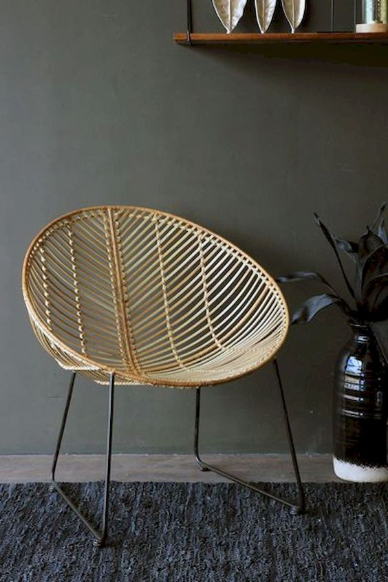 a round rattan chair on black metal legs is a stylish addition to many space