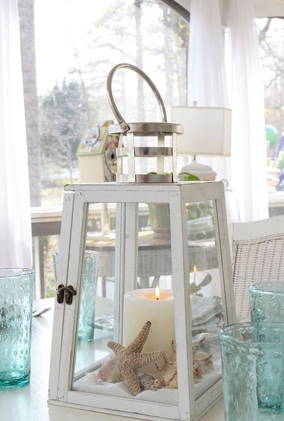 a white lantern with sand, starfish, seashells and a large candle will brign a strong beachy feel to the space