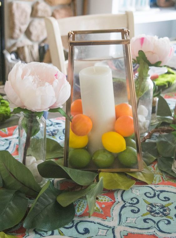 a copper lantern filled with faux lemons, limes and peaches and with a large pillar candle