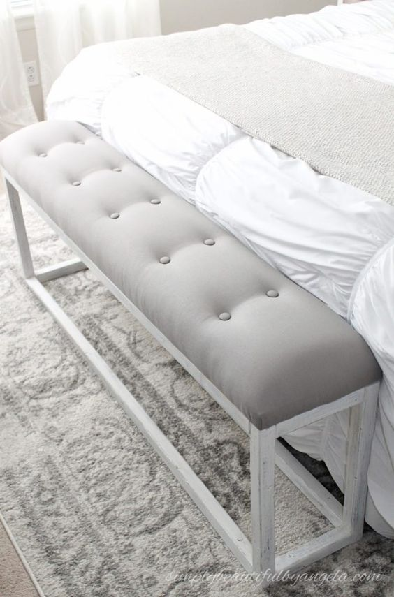 a simple and sleek upholstered and tufted bench with a whitewashed frame for a rustic bedroom