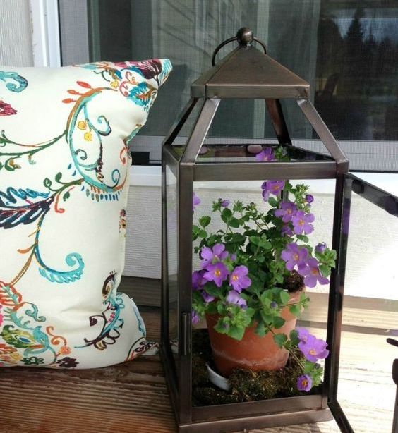 a lantern with purple blooms in a planter is a very easy outdoor decoration that can be made in a second