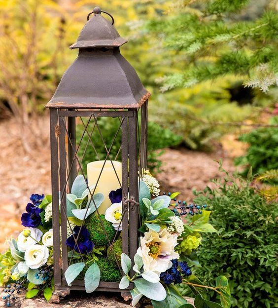 a vintage lantern filled with moss balls and with fake blooms and greenery won't wither fast