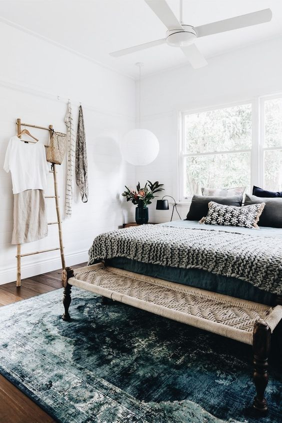 a wicker and macrame bench highlights the boho chic style of the bedroom