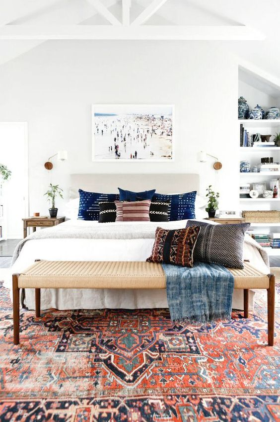 a wicker bench matches the boho chic bedroom abd adds texture to the space
