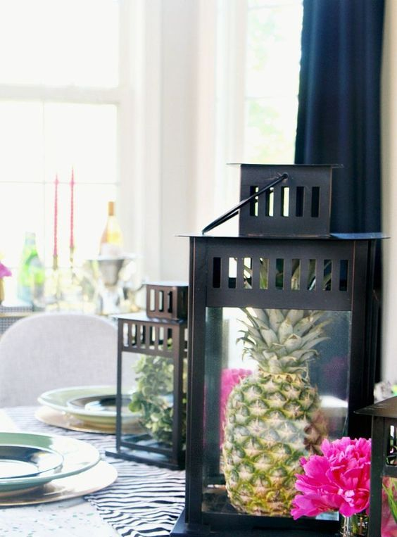 black lanterns with succulents in one and a pineapple in another feel very summery-like