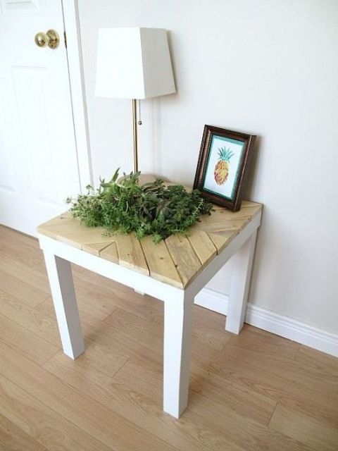 an IKEA Lack table turned into a refreshing piece with pallet wood on top and some greenery growing inside