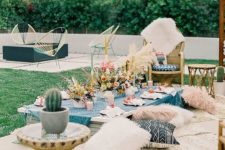 03 a bright and welcoming baby shower picnic setting with lots of pillows, blooms and pampas grass