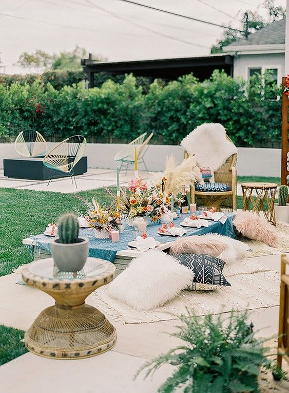 a bright and welcoming baby shower picnic setting with lots of pillows, blooms and pampas grass