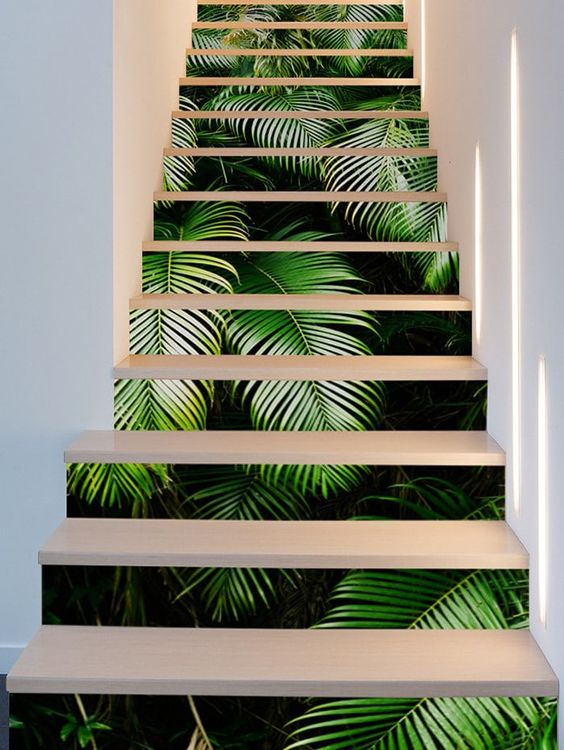 a laconic and even minimalist staircase with tropical leaf print decals to spruce it up for summer