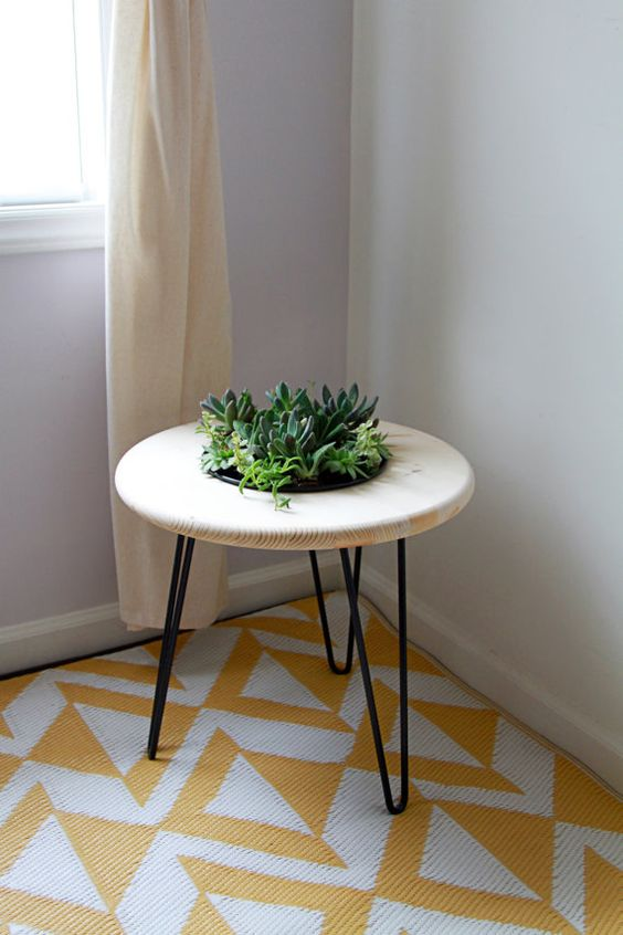 a chic side table with hairpin legs and a built-in planter in the center will refresh your space at once