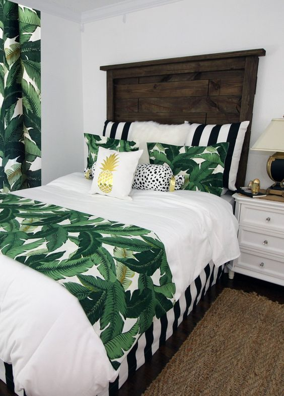 tropical leaf prints on the bedding and curtains are easy to add a bold summer look to the bedroom