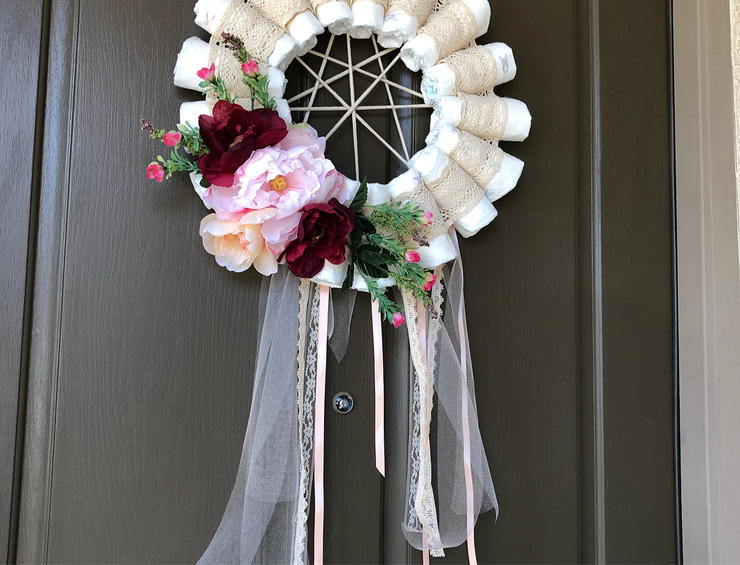 a funny diaper dream catcher with ribbons, fresh blooms and greenery is a cool decoration