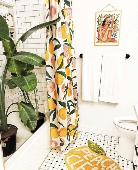 a citrus shower curtain and a peach rug make this bathroom summer like and welcoming