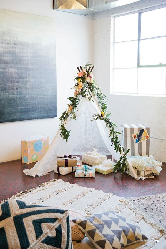a lace teepee decorated with greenery and fresh blooms is a cute idea for a boho baby shower