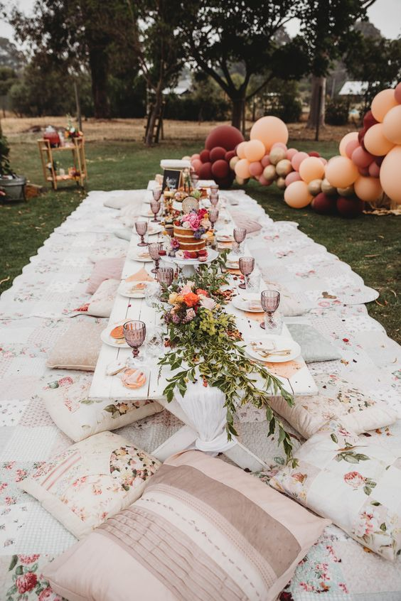 a boho baby shower picnic setting with bright florals, balloons and floral pillows for a girl's party