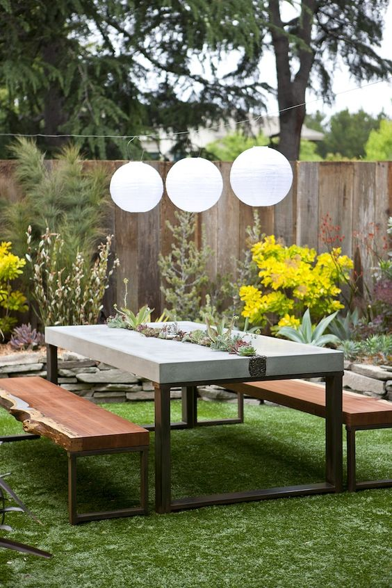 a concrete dining table with a planter in the center and succulents and greenery growing is very chic and trendy