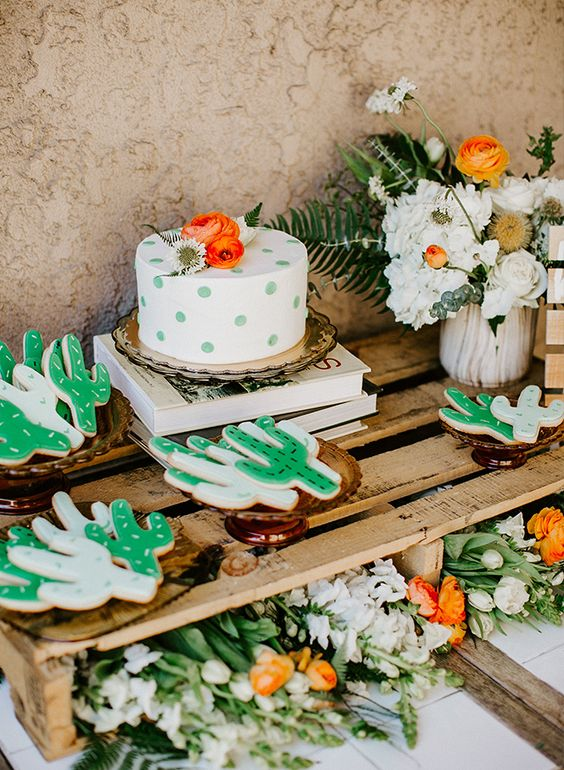 a polka dot baby shower cake and cactus-shaped cookies are amazing for your boho desert baby shower