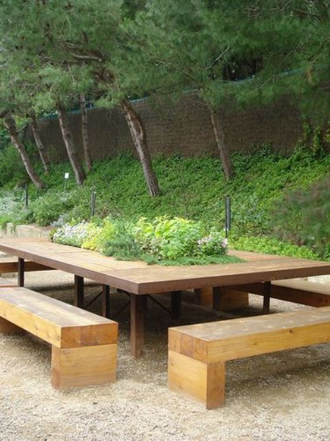 a weathered wood dining table with a planter with greenery in the center plus wooden benches for outdoors