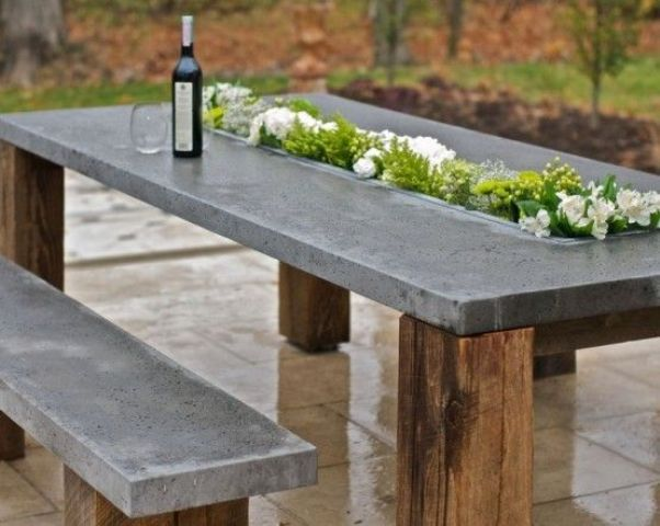 an outdoor concrete dining table with a planter in the center looks very contrasting and very fresh