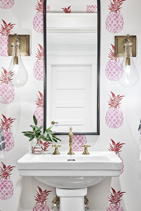 a fun and whimsy powder room with pink pineapple print wallpaper feels summer-like