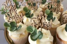15 gorgeous cupcakes topped with wooden topeprs and fresh eucalyptus are ideal for a gender neutral boho shower