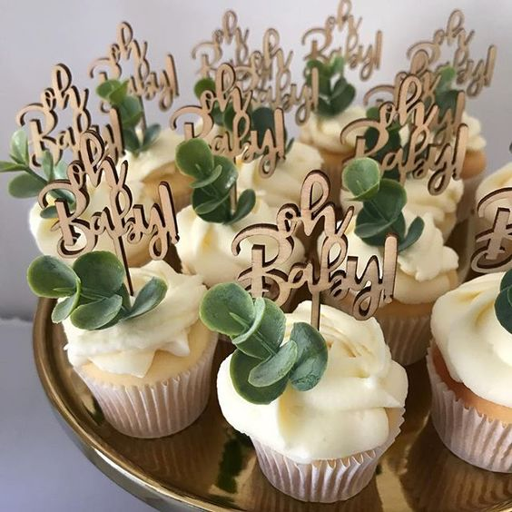 gorgeous cupcakes topped with wooden topeprs and fresh eucalyptus are ideal for a gender neutral boho shower