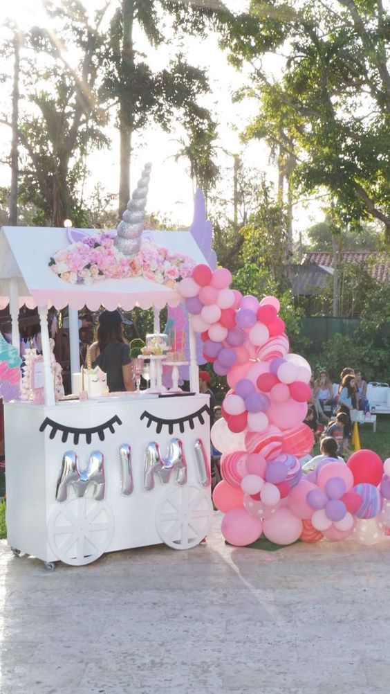 a dessert table with lots of balloons for a Unicorn birthday party, perfect and very cute