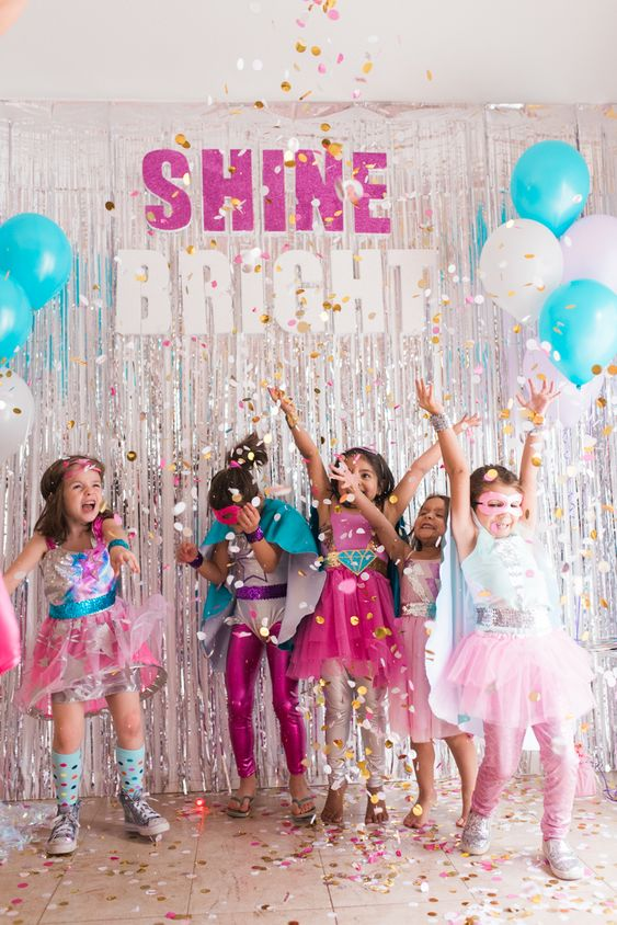 colorful Superhero themed party for girls with bright costumes and lot sof glitter and confetti