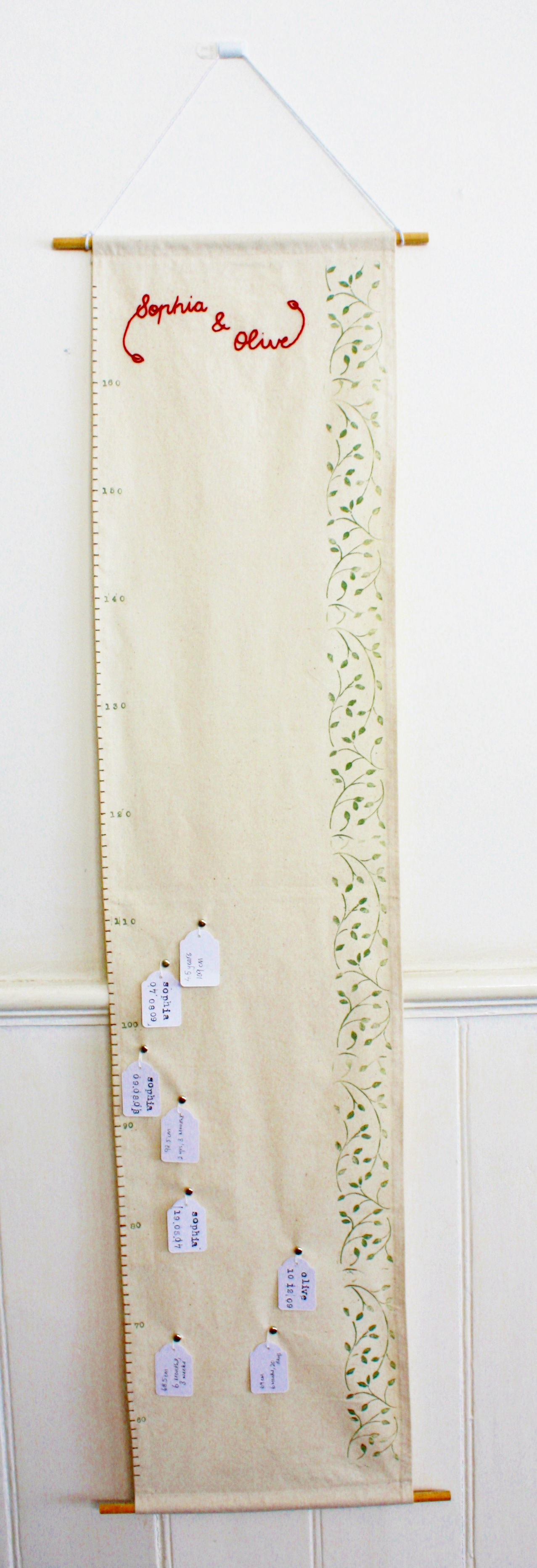 DIY fabric growth chart with tags on decorative nails