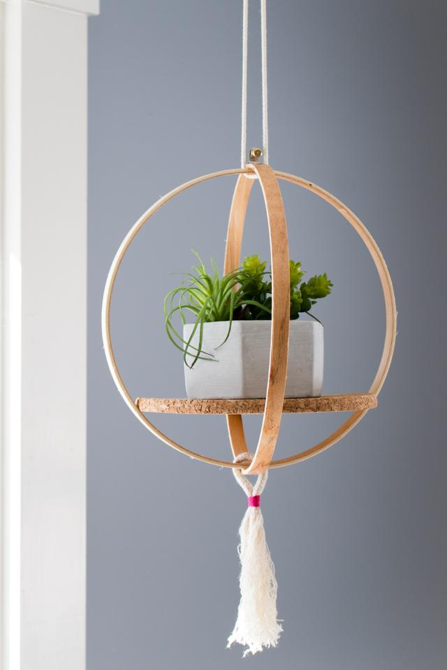 DIY hanging shelf of embroidery hoops, cork and tassels (via stitchedmodern.com)