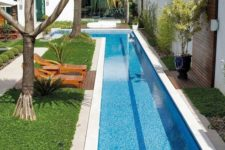 02 a contemporary backyard with a long and narrow L-shaped pool, green grass, loungers and trees