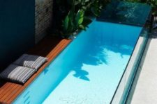 02 a tiny wooden deck is paired with a long and narrow pool made of glass – such a steup will fit even the smallest outdoor space