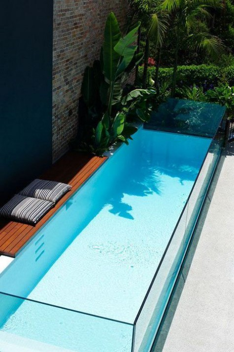 a tiny wooden deck is paired with a long and narrow pool made of glass - such a steup will fit even the smallest outdoor space