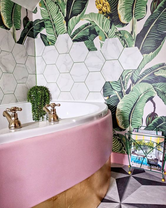 a glam bathroom with a palm leaf print wallpaper and marble hexagon tiles plus a pink tub