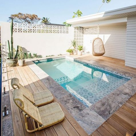 a hanging wicker chair and some wicker loungers plus potted plants are all you need by the pool