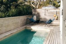 04 a chic contemporary backyard fully done with a wooden deck, butterfly chairs and a long and narrow pool