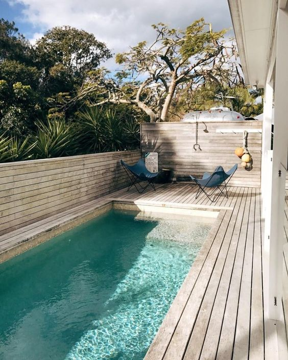 a chic contemporary backyard fully done with a wooden deck, butterfly chairs and a long and narrow pool
